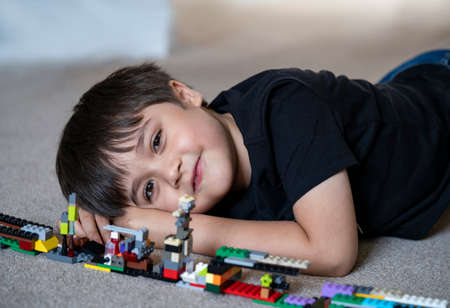 Portrait kid playing plastic blocks, Happy Child boy lying on carpet floor  bluiding his colouful blocks toys, Young boy with smiling face looking at camera while laying on floor.