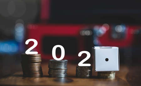 Number 202 and white paper dice showing number one on stacks British pound coins, Financial planing for 2021 New Year resolution for saving money for the future in business or personal life concept 版權商用圖片