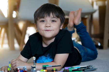 Portrait kid playing plastic blocks, Happy Child boy lying on carpet floor building his colourful blocks toys, Young boy with smiling face looking at camera while laying on floor. 版權商用圖片 - 152656680