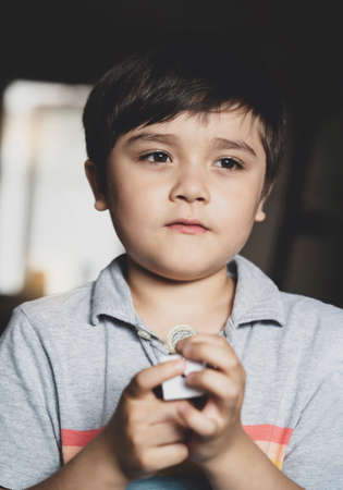 Portrait young boy standing alone holding money with thinking face, Selective focus Child boy holding one pound coin with deep in through,  Children learning to save money for studying or future