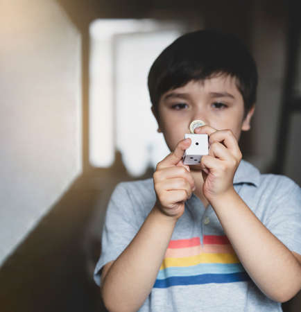 Blurry face of Kid holding one pound coin and white paper dice showing number one with copy space for text, Selective focus of  hild boy showing momey one pound for saving money for future.