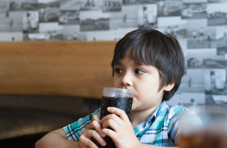 Side view Prtrait of Cute kid sitting on table drinking cold drink in restaurant, Toodler drinking soda or soft drink with straw, Child boy waiting for foo in cafe 版權商用圖片