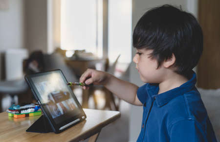 School Kid using tablet  taking with his class friends, Child showing his plastic toys to his friends , Young boystudying online on touch pad, new normal life stye with learning online, Distance education