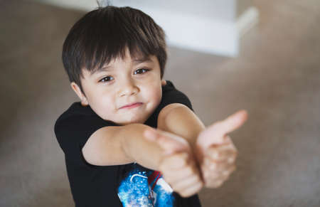 Top view head shot kid looking up with copy space, Candid young boy looking at camera withs miling face, Selective focus Child sitting on floor showing thumbs up. 版權商用圖片