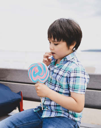 cute kid eating lollipop, Happy little boy holding big sugar candy, Child with smiling face eat sweets, Active childhood enjoying fun time outdoor in sunny day summer