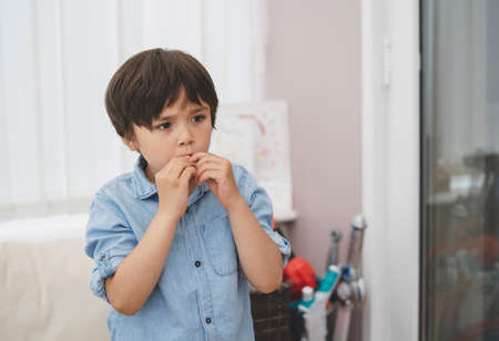Portrait of kid biting his finger nails while looking at something, Emotional child portrait standing alone with thinking face,Young boy putting finger in his mouth.
