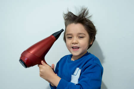 Candid shot, cute kid drying his hair with hair dryer, Cheerful 6 years old boy try to making his hair like a crazy expression, flying hair, Lightness and happiness. Concept child care concept 版權商用圖片