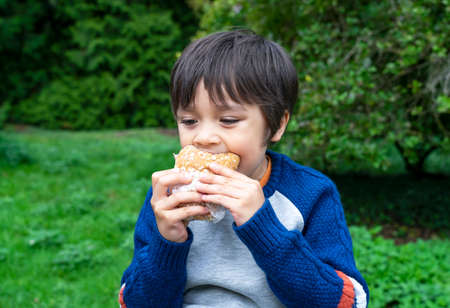 Hungry boy eating homemade bread sandwiches with mixed vegetables in the park, Child siting on green grass eating his snack picnic with blurry trees background, Spring outdoor activity 版權商用圖片