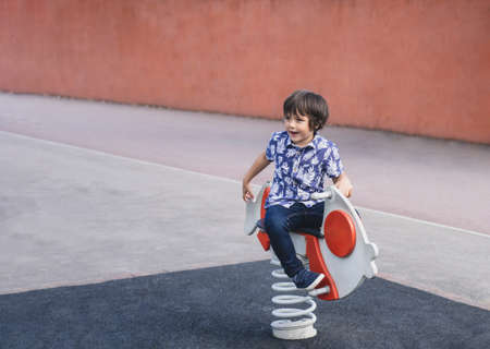 Active kid sitting on rocking chairs in the playground, Happy Child boy having fun playing outdoor in the park on Summer.