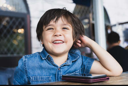 Portrait happy kid looking out with smiling face, Little boy watching cartoo or play games on mobile phone while waiting for food in cafe, Children with Technology concept.