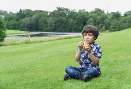 Hungry kid boy eating homemade bread sandwiches with mixed vegetables, Child siting on green grass eating his snack picnic in the park. Summer holidays in the camp