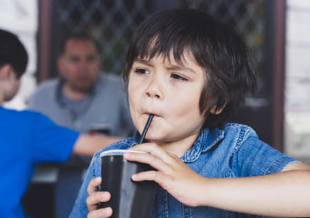 Cute toddler boy drinking cold drink, Happy Child sitting in cafe drinking soda or soft drink with a straw, Unhealthy drink for Children concept