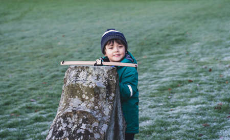 Portrait of happy kid with smiling face standing behind old wall holding crossbow,  Active child boy hiding behind stone brick  shoot a toy crossbow, Outdoor activity during cold weather Winter
