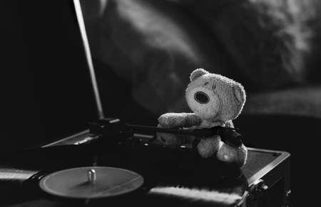 Still life shot of morning light stream through lonely teddy bear sitting on spinning record vinyl player, Low key light image Brown bear sitting alone in drak room. Emotional black and white photo 版權商用圖片