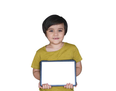 Selective focus happy 7-8 year old kid with smiling face holding blank tablet on white background, New normal life, child boy using tablet learning at home, Home schooling,E-learning online education