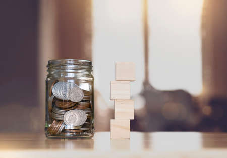 Sterling pound coin and pennies nickels in clear jar with mock up empty stack wooden on table with blurry inside house background,Financial planing for New Year resolution for saving money for future 版權商用圖片
