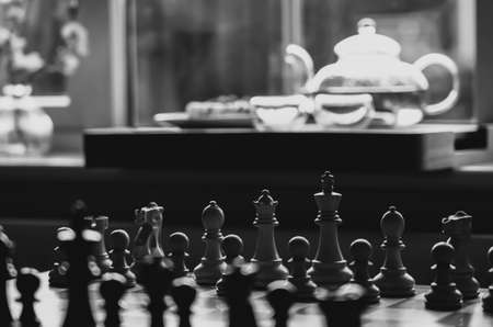 Selective focus of wood chess pieces on board game with blurry tea pot next to window background in black and white, Homely and Cosy scene for Autumn and winter background