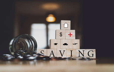 British sterling coin falling out from jar with SAVING word and sign or symbol on wooden cube with blurry dark room background,Financial planing New Year resolution for saving money for future life