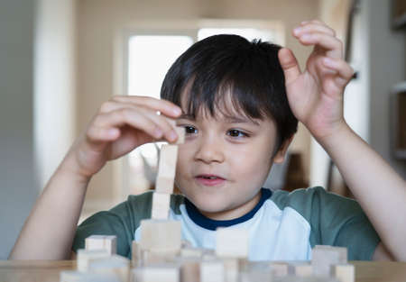 Selective focus smart kid building the tower stack from wooden blocks toy, Happy Child boy playing stack of wood cube in living room,Children Play and learn about construction at home,Home schooling 版權商用圖片