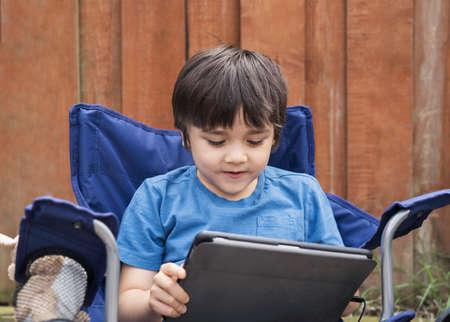 Active kid sitting on chair in the garden playing game or watching cartoons on tablet, Handsome young boy relaxing in the garden on sunny day summer, New normal lifestyle concept 版權商用圖片
