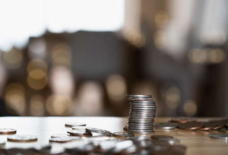 Stack British money sterling pound coins on wooden table, Selective focus GBP coins on the table with blurry bokeh light in dark room, Business and financial for money saving or investment concept Stock Photo