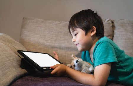 Cropped shot kid lying on sofa watching cartoons on tablet,6-7 year old boy playing game on touch pad, Children having activity on his own with mock up of digital tablet.New normal  education 版權商用圖片