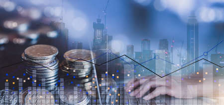 Double exposure of trading graph, stack sterling coin and hand typing on laptop with blurry building in london at night, The Image can us for Business and financial investment background concept