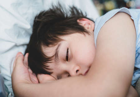 Cropped shot Child boy sleep with his eyes half open on his bed, Close up Young Kid sleeping with open eyed while taking a nap, Sleep problems in young children concept or REM sleep 版權商用圖片