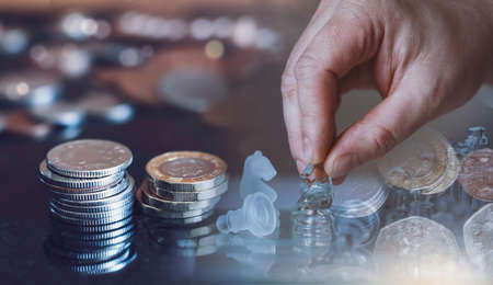 Double exposure of hand of businessman moving chess  knight competition with stack sterling coin, Business leader and confrontation solve problems concept, Chess horse on board with copy space 版權商用圖片