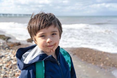 Head shot Kid with dirty mouth of chocolate ice cream with blurry sea view background,Candid shot happy child standing alone and looking at camera with smiling face.A boy playing outdoor in the summer