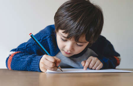 Portrait of school kid boy siting on table doing homework, Child holding pencil writing, A boy drawing on white paper on table, Elementary school and homeschooling concept 版權商用圖片