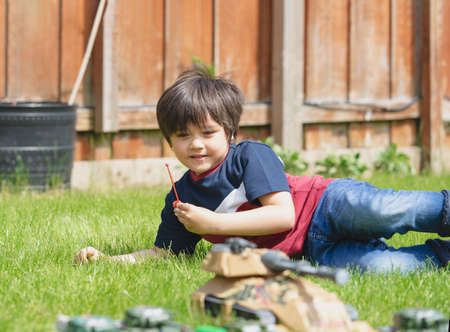 Active boy laying down on the grass playing with soldiers and tank toys in the garden,Kid playing wars and peace on his own in hot sunny day summer,Children imagination and development