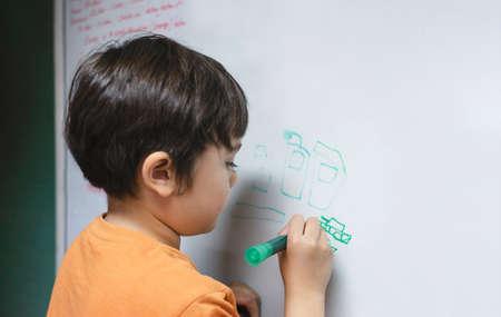 Portrait school kid drawing cartoon tank on white board, Child boy holding colour pen write on board, Home schooling, Education concept