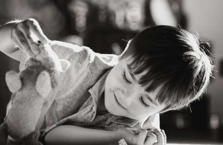 Black and white image new normal lifestyle, Candid shot kid lying on floor playing with dog toy