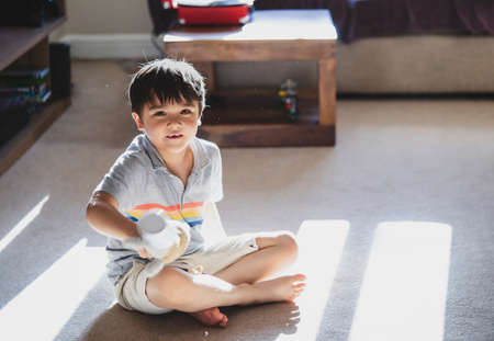 Kid playing alone with dog toy in living room with morning sun shining through the window