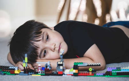 Emotional portrait Unhappy kid lying down on wooden floor with his plastic blocks toy