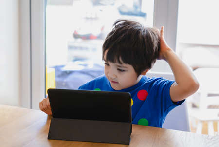 School Kid using tablet for his homework, Child looking at digital tablet with thinking face, Young boy watching cartoon on touch pad, new normal life stye with learning online, Distance education