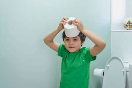Cute boy sitting in the toilet playing with toilet paper,kid boy sitting in the restroom and putting  toilet roll on his head, Child holding  white tissue, Children health care concept