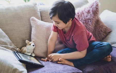 Mixed race kid sitting on sofa watching cartoons on tablet,Portrait 6-7 year old boy playing game on touch pad, Cute Kid having fun and relaxing on his own in living room, New normal lifestyle