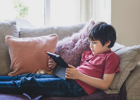 Mixed race kid sitting on sofa watching cartoons on tablet,Portrait 6-7 year old boy playing game on touch pad, Cute Kid having fun and relaxing alone in living room, New normal lifestyle 版權商用圖片