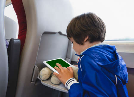Kid traveling by the train, Child drawing or watching cartoon on teplet sitting by the window. Little boy in a high speed express train on family vacation, Entertainment for young passenger. 版權商用圖片