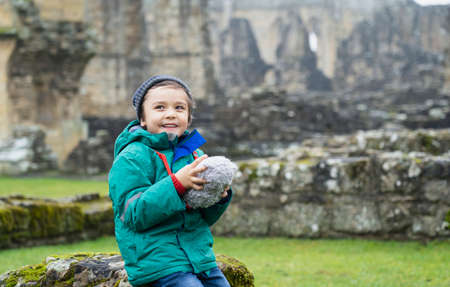 Portrait of School kid taking teddy bear explore with his learning history, Happy child boy wearing warm cloths holding his soft toy sitting on old brick wall with blurry ruins of old abbey background 版權商用圖片