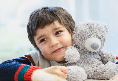 High key light portrait cute boy laying his head on teddy bear and looking out with beautiful brown eyes, Adorable Child playing with toys and relaxing while waiting for food in cafe.