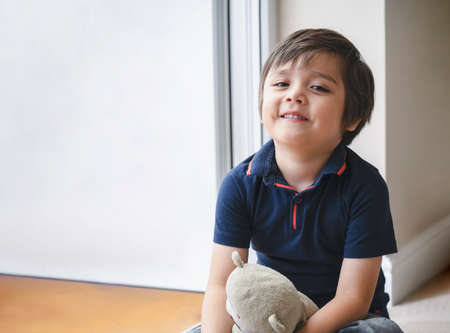 Portrait of happy kid sitting on wooden floor playing with teddy bear, Cute boy play with his soft toy, Positive child relaxing at home. child stay at home during covid-19,Social Distancing