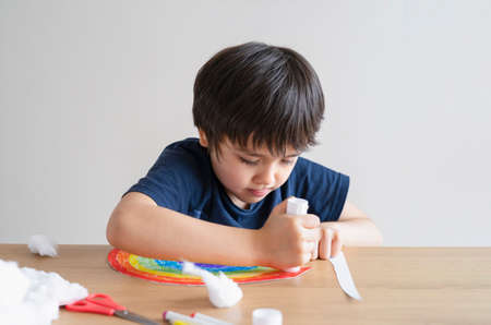 Kid putting glue stick on paper for sticking cotton wool as decorative elements for clouds on rainbow. Child Boy enjoy art activity at home. home schooling and distance learning concept