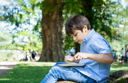 High key light portrait of kid eating picnic under big tree on sunny day in summer, Active child boy having fun enjoying his home made lunch with parent in the park, New normal Healthy lifestyle