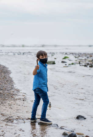Full length portrait Kid wearing protective face mask for pollution or virus, Mixed race asian - caucasian 6 year old, Child wearing protection mask while playing by the sea, Concept for Corona or Coronava virus and pm 2.5