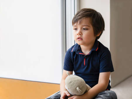 Emotional portrait sad kid sitting with teddy bear, Lonely kid sitting on floor in corner and looking down,Little boy wall corner punishment sitting,Family violence concept. 版權商用圖片