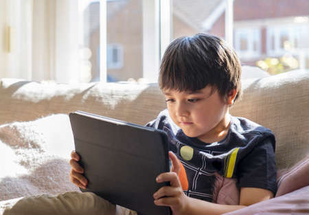 High key kid sitting on sofa watching cartoon on tablet,Happy boy playing game on touch pad with bright light in morning. ute Kid having fun and relaxing on his own in living room,New normal lifestyle