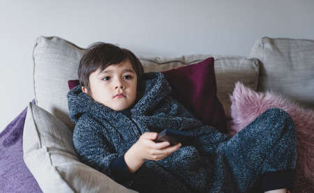 Cute kid sitting on sofa holding remote control, A happy child boy relaxing at home watching TV during cold weather outside in Autumn or Winter. Indoors activities for kids during bad weather